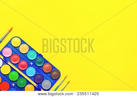 Blue Palette With Rows Of Multicolored Watercolor Paints Brushes On Bright Yellow Background. Arts S