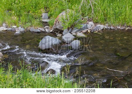 Fresh Water Rolling Over Rocks In A Wild Creek. Higihwood, Montana, Usa In Spring Or Summer.