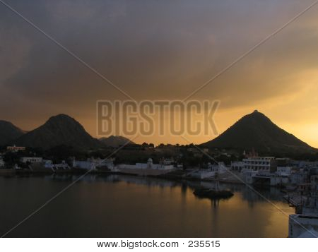 sunset in pushkar lake, india. pushkar lake is an artificial lake in rajasthan state of western india. it is located near the town of pushkar in ajmer district. the lake was created in the 12th century when a dam was built across the headwaters of the lun poster
