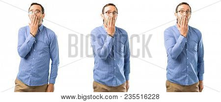 Middle age handsome man covers mouth in shock, looks shy, expressing silence and mistake concepts, scared over white background
