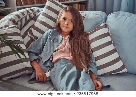 Portrait Of A Cute Little Girl With Long Brown Hair And Piercing Glance, Looking At A Camera, Lying