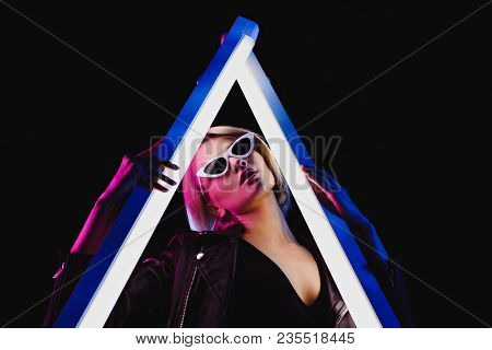 Fashionable Girl Posing With Two Ultra Violet Lamps For Vogue Shoot, Isolated On Black
