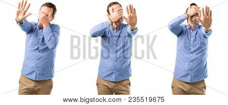 Middle age handsome man stressful and shy keeping hand on head, tired and frustrated over white background