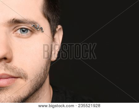 Young man with pierced eyebrow on black background, closeup