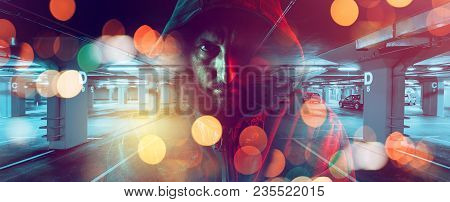 Car Thief Conceptual Image With Hooded Criminal Man Overlaying Image Of Underground Parking Garage