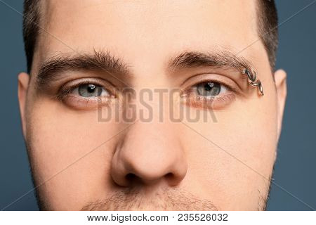 Young man with pierced eyebrow on color background, closeup