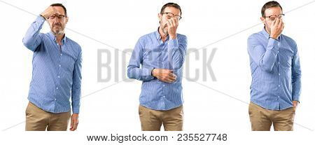 Middle age handsome man with sleepy expression, being overworked and tired, rubbes nose because of weariness over white background