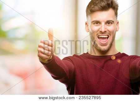 Handsome young man stand happy and positive with thumbs up approving with a big smile expressing okay gesture