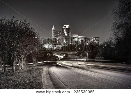A Black And White Cityscape View Of Raleigh, North Carolina At Night.