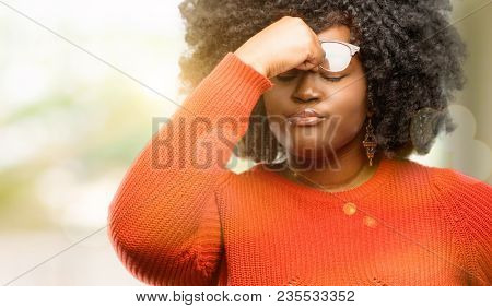 Beautiful african woman with sleepy expression, being overworked and tired, rubbes nose because of weariness, outdoor
