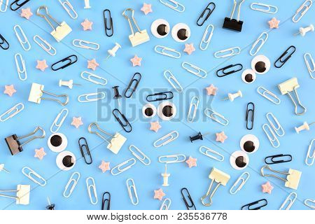 Strange, Cheerful Background. Stationery And Puppet Eyes Make Up A Pattern On A Blue Background. Pho
