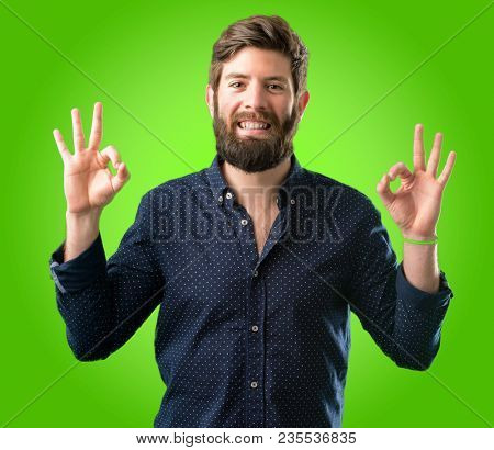 Young hipster man with big beard doing ok sign gesture with both hands expressing meditation and relaxation over green background
