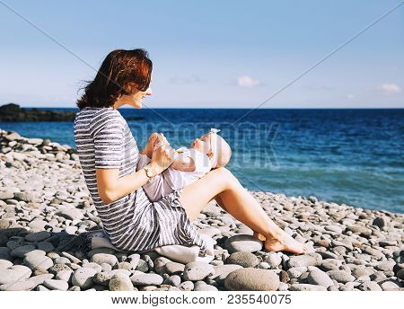Happy Young Family. Mother And Baby Playing Outdoors On The Sea Beach. Portrait Loving Mom With Daug
