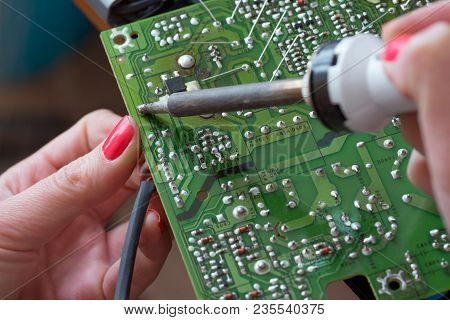 The Girl-engineer Repairs A Switching Power Supply. Installation And Soldering Of Electronic Compone