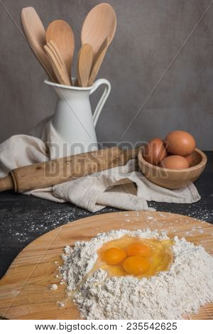Eggs, Dough, Flour And Rolling-pin On Wooden Table Background. Preparation For Making Homemade Ravio