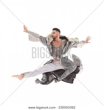 Young strong man wearing  oriental costume dances on a white background.