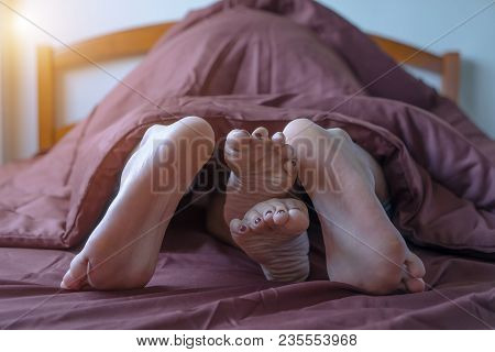 Close Up Couple Feet Lying In Bed.  Male And Female Feet On Bed - Loving Couple Having Sex Under Bla