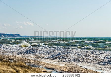 Waves Splashing On The Remaining Ice Along A Beach On Lake Michigan With A Lighthouse In The Backgro