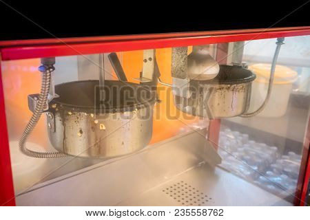 A Closed Up Look Of Double Popcorn Maker Pots Through The Cabinet With Blurred Background