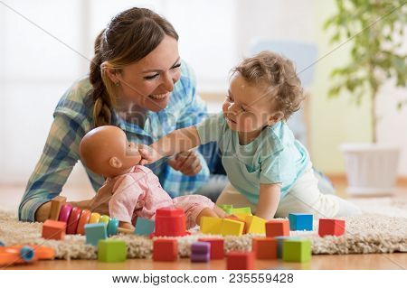 Adorable Baby Boy Playing With Doll In Nursery Room. Happy Healthy Child Having Fun With Colorful Di
