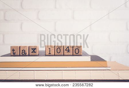 The Word Tax 1040, Alphabet On Wooden Cubes On Top Of Books. Background Copy Space, Vintage Minimal