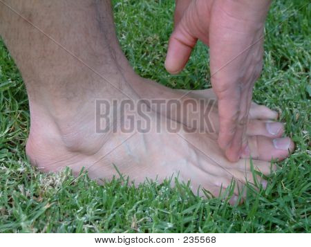 Young Man Touches His Toes With His Fingers