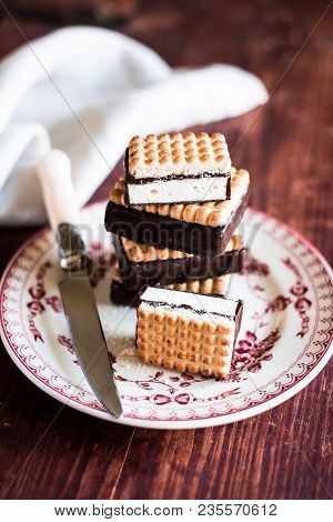 Sandwich Cookies With Vanilla Souffle In Dark Chocolate Coating Stacked On A Dessert Plate On A Wood