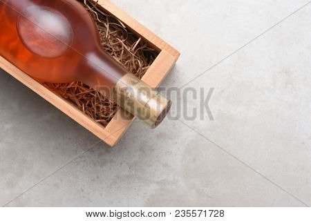 White Zinfandel, Blush Wine: A bottle of Rose wine in a wood box with packing straw. Item is positioned in the upper right corner with copy space.