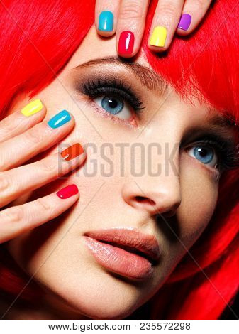 Closeup face of a beautiful  girl with bright multicolor nails. Gorgeous and stunning  woman with brown stylish eye makeup of eyes.