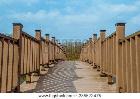 Closeup Perspective Of Wooden Footbridge With Trees And Partly Cloudy Blue Sky In Background.