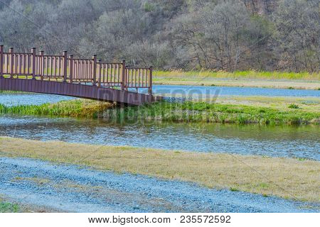 Landscape Of Wooden Footbridge Over A Pond Next To Gravel Road With Tree Covered Mountain And Blue S