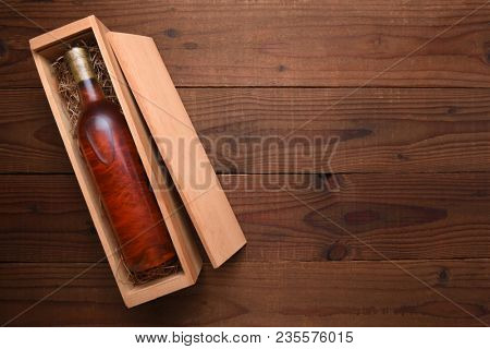 Blush Wine Box: A single Bottle of White Zinfandel wine in its wooden case on a dark wood table with copy space.