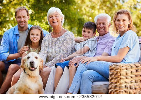 Three generation family sitting with pet dog in the garden