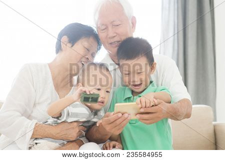 Portrait of happy Asian grandparents and grandchildren taking self photo using smart phone at home, family indoor lifestyle.