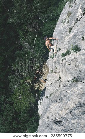 Man Rock Climber Climbs On The Cliff. The Climber Climbs To The Top Of The Mountain.