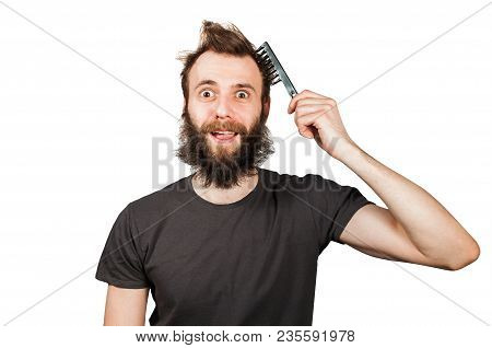 Young Bearded Overgrown Man Holding Comb And Combing His Hair. Isolated On White.