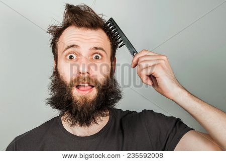 Young Bearded Overgrown Man Holding Comb And Combing His Hair. Close Up Portrait.
