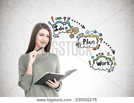 Smiling Young Woman Wearing A Gray Sweater Is Holding A Planner And A Pen. A Concrete Wall With A Co