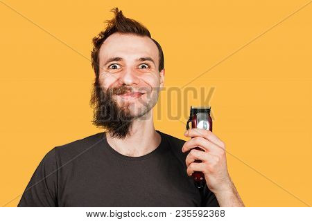 Man With Half-shaved Beard Surprised With Wide Eyes Holding Hair Clipper. Isolated On Orange.