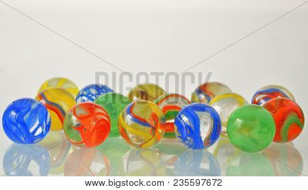 Close Up Of A Bunch Of Marbles On Glass Table
