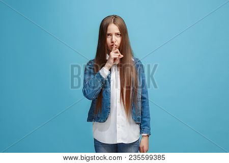 Secret, Gossip Concept. Young Teen Girl Whispering A Secret Behind Her Hand Isolated On Trendy Blue