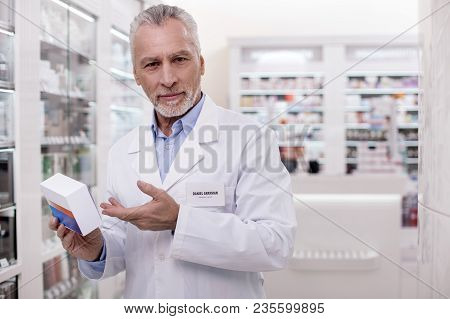 Experienced Pharmacist. Senior Appealing Male Pharmacist Gazing At Camera While Carrying Medication