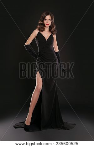 Elegant Lady In Long Sexy Dress With Retro Wavy Hairstyle Posing Isolated On Studio Black Background
