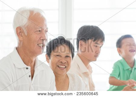 Candid of happy Asian family relaxed at home, multi generations people indoor lifestyle.