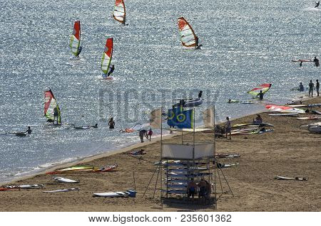 The Beach On The Mediterranean Sea With The Tourists And The Windsurfers Riding On The Cape Prasonis