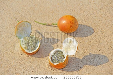 Three Orange Open Passion Fruit With Seeds. Passion Fruit Closeup On The Beach, On The Sand And On T