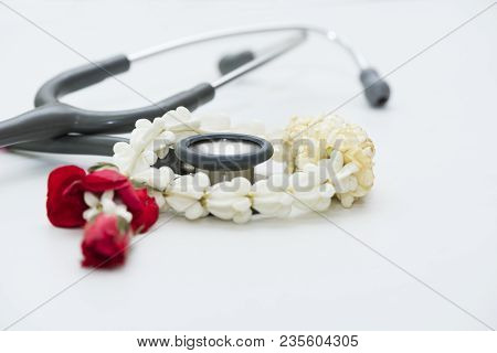 A Stethoscope And White Jasmine Garland On White Background. The Jasmine Garland Giving To Doctor Fo