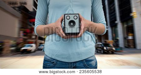 Composite image of mid section of female photographer holding vintage camera