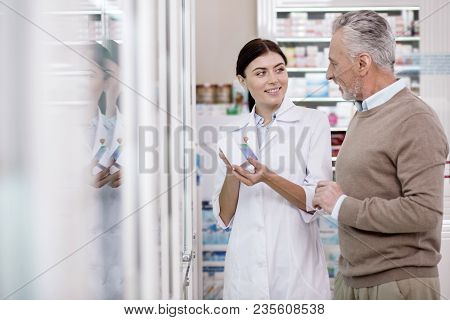 Helpful Medication. Joyful Female Pharmacist Explaining Mature Man Side Effect While Carrying Medica