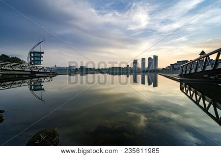 Stunning Morning View Near The Lakeside, Modern Building And Wooden Jetty. Dramatic Clouds And Sunli